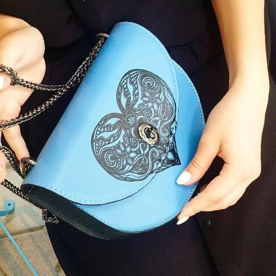 A blue half-moon bag with a black heart